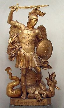 """Statue of Archangel Michael slaying Satan represented as a dragon. Quis ut Deus is inscribed on his shield - a Latin sentence meaning """"Who [is] like God?""""."""