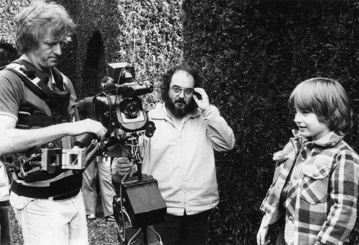 Stanley Kubrick on the daytime exterior set of The Shining's Hedge Maze, with actor Danny Lloyd and Steadicam operator Garrett Brown.