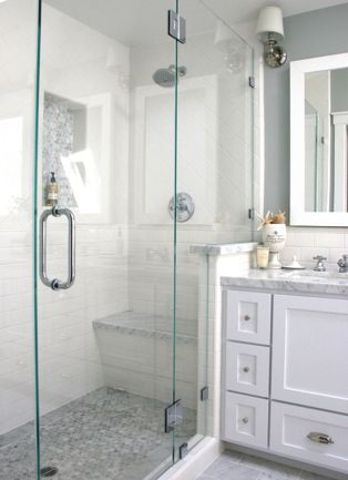 shower butted up to vanity, stub wall, seat. glass door