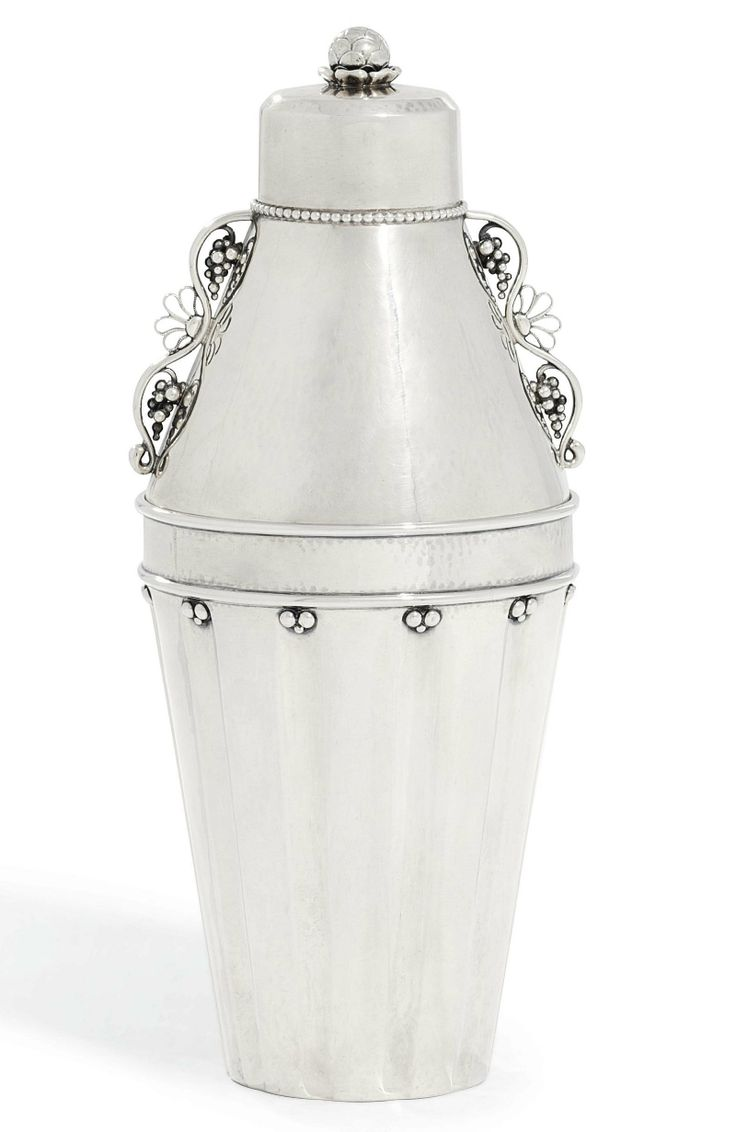 A DANISH COCKTAIL SHAKER DESIGNED BY GEORG JENSEN MARK OF GEORG JENSEN, COPENHAGEN, 1925-1932 Fluted tapering, the top of each flute applied with beads, the tapering cover applied with fruiting scrolls and with a further cover with flowering finial, with pierced internal grill, no. 497, marked underneath 9½ in. (24 cm.) high