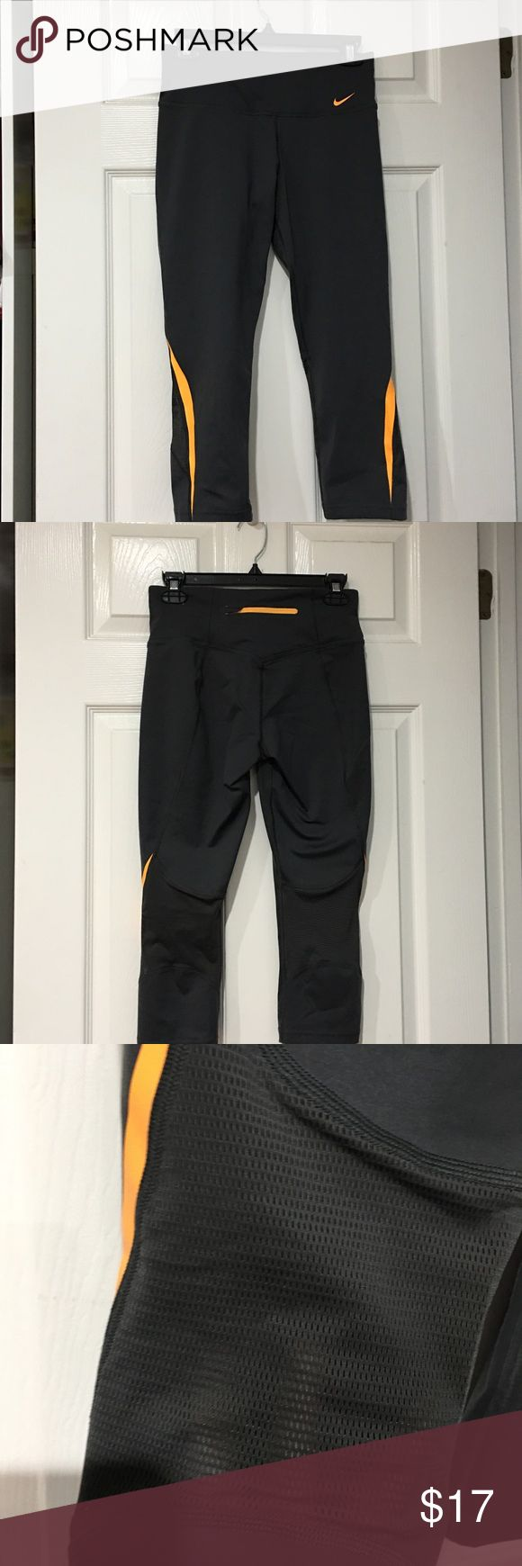 Nike Dri-Fit Mid-Calf Yoga Pants Dark  Grey colored Nike yoga pants with orange accents on the bottom of pants. Has mesh detail behind the knee. Excellent condition, worn a few times. Nike Pants Leggings