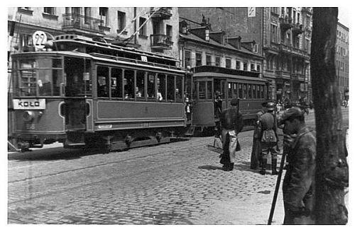 """Tramwaj nr """"22"""" na trasie PLAC TEATRALNY-KOŁO w 1940 roku. Po prawej stronie widoczny patrol Schutzpolizei legitymujący przechodniów."""