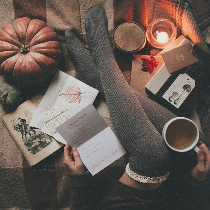 Cosy autumn vibes with woolen tights, letters, low lighting, hot drinks and a pumpkin.