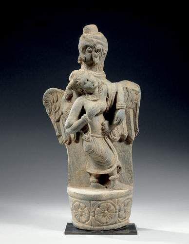 Stèle en schiste représentant un garuda debout sur un socle tenant une jeune femme, le socle orné d'une frise de rosaces. Gandhara, IIème / IVème siècle. Dimension : 51 x 26 cm.