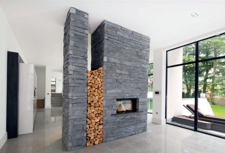 Contemporary Living Room by theCAVE architecture + design | Stone cladding slate finish fireplace.