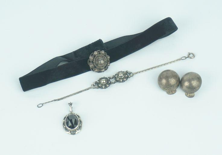 Een zilveren Zeeuwse knoop aan zwart lint, een zilveren armbandje met 2 Zeeuwse knopen, een zilveren hanger bezet met facetgeslepen granaat en een paar zilveren halve bol-oorclips