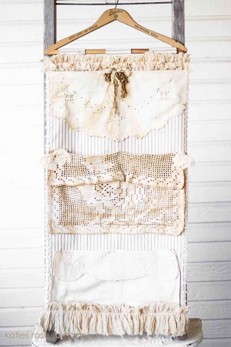Vintage pocket wall hanging made with ticking, lace & linens, hanging on a vintage hanger.
