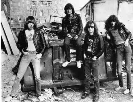 1970s NYC // Johnny, Dee Dee, Tommy and Joey Ramone are standing alongside a wrecked car in a garbage-strewn alley; a truck emblazoned with the CBGB logo can be seen in the rear.