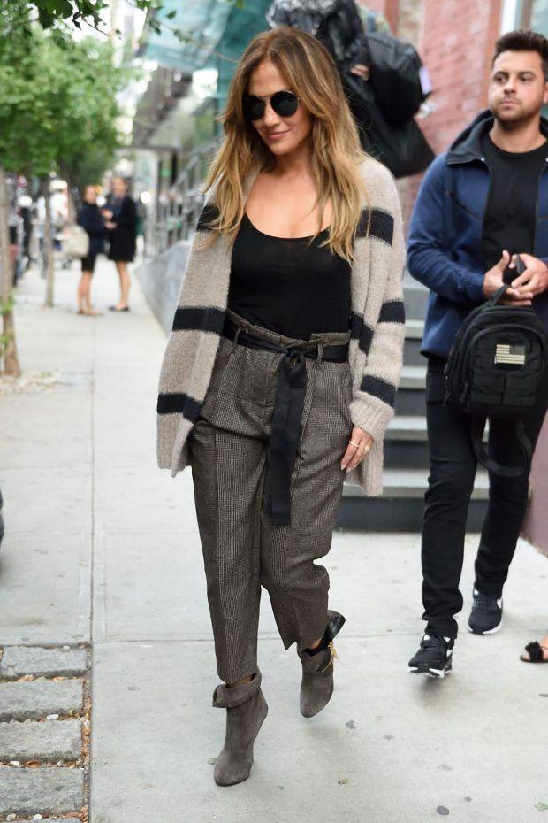 Street style look de Jennifer Lopez com botinha de camurça cinza, calça combinando com laço em forma de cinto e casaco bege com listras pretas