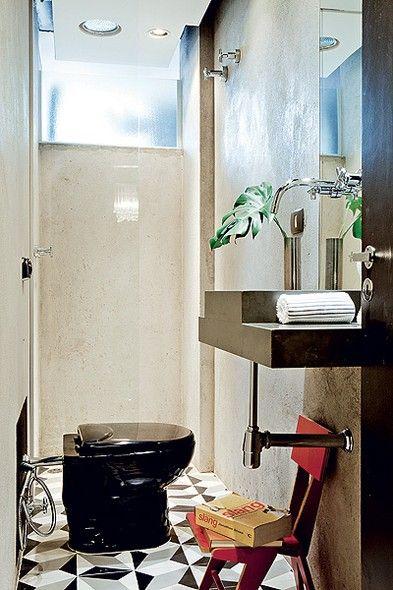 O lavabo tem piso de ladrilho hidráulico e paredes com o reboco impermeabilizado. Embaixo da bancada de ardósia, a cadeira de Zanine Caldas decora e dá suporte para livros e revistas. Casa do designer de interiores Sandro Brasil