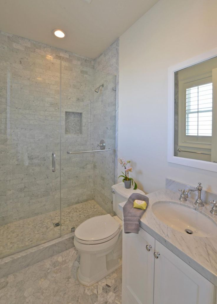 Soft shades of white and gray gleam in the stunning Carrara marble tile in this bathroom. Neutral walls, a white-framed mirror and a white vanity accentuate the marble's subtle yet eye-catching color.