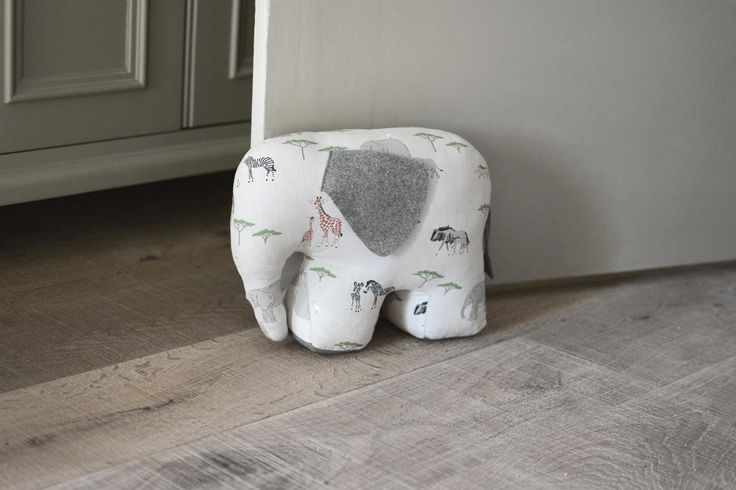 Elephant Door Stop | Sophie Allport | Our selection of door stops are the perfect gift to make any house a home. This cute elephant will stop your doors banging in style! It's both decorative and practical and will liven up any room. Especially good for a playroom or child's bedroom.  Made from our Safari fabric it features elephants, giraffes, rhinos, zebras, warthogs and wilderbeast on a dusty white background.