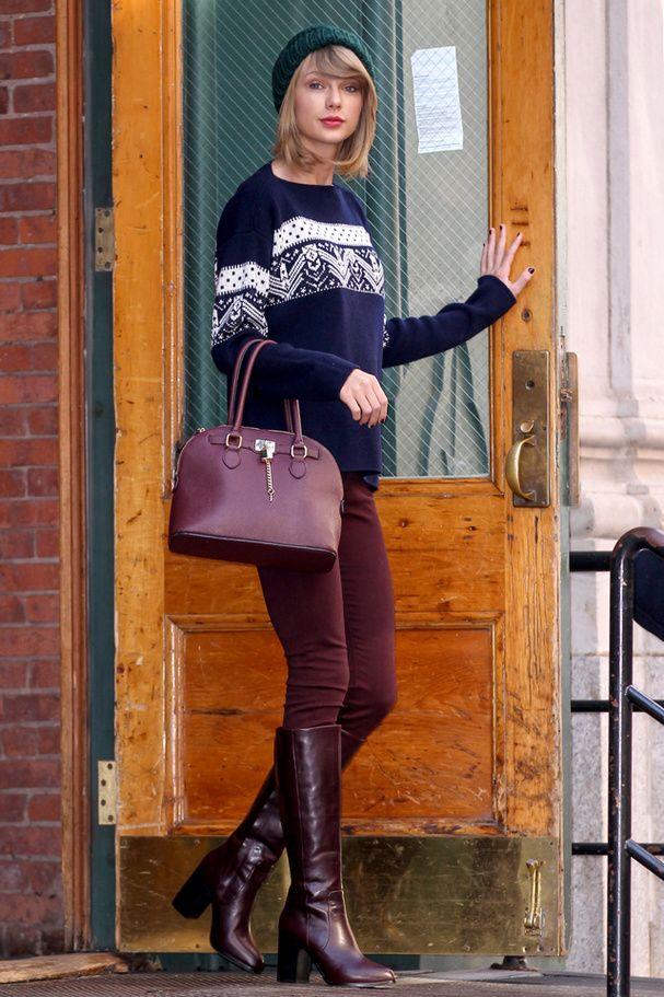 Le look de Taylor Swift:  pull bleu à grosse maille, jean bordeaux et bottes vintage à talons. Elle accessoirise sa tenue avec un bonnet vert sapin et un sac assorti à ses bottes.