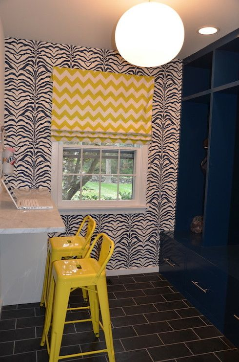 Navy blue and yellow mud room features accent wall clad in Rose Cumming Zebrine Wallpaper which frames the sash window dressed in a yellow chevron roman shade adjacent to a bar height built-in desk lined with yellow Tolix Barstools.