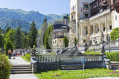 View of Peles castle with unidentified tourists having a walk on the alleys on July 24, 2013 in Sinaia, Romania. Peles castle was declared museum in 1953 and is the most visited in Romania with more than 300.000 tourists every year.