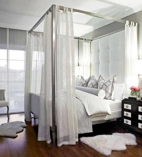 Heavenly White Master Bedroom    Canopy sheers frame the bed's tall tufted headboard in the master bedroom. Fluffy sheepskin rugs add to the plush comfort of the space.