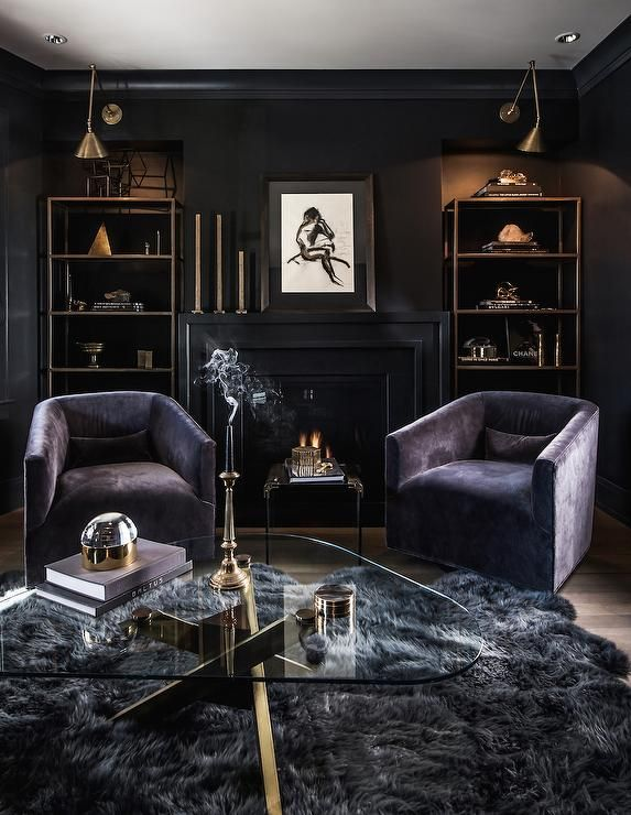 Contemporary living room features a black fireplace topped with a nude abstract sketch and modern brass candle holders flanked by niches filled with brass etageres illuminated by Boston Functional Library Wall Lamps. A pair of purple accent chairs and a glass and metal table stand in front of the fireplace facing a glass and brass coffee table atop a gray sheepskin rug