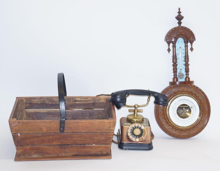 Een baro- thermometer op gesneden paneel, daarbij een oude telefoon