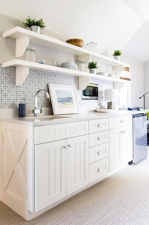 White butler pantry boasts boasts stacked white shelves on corbels mounted above white beadboard cabinets finished with an x-trim, polished nickel hardware, and a gray quartz countertop.