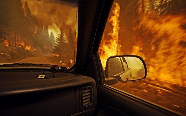 Bombeiro observa, relativamente em segurança dentro de caminhonete, incêndio florestal em Montana, nos EUA