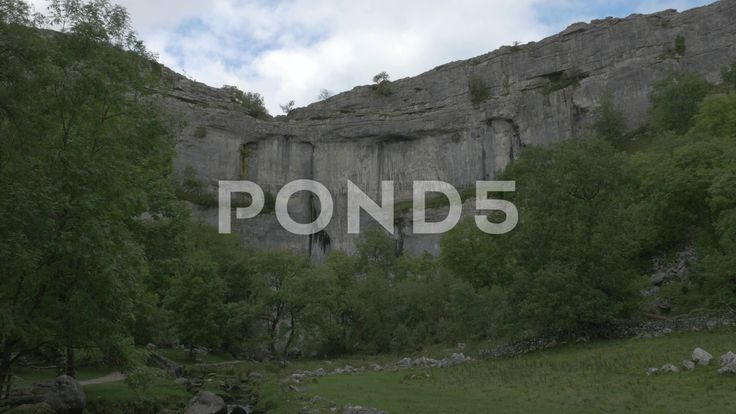 4K Huge Cliff Face of Malham Cove Lime Stone Rocks Trees Low Angle - Stock Footage | by RyanJonesFilms