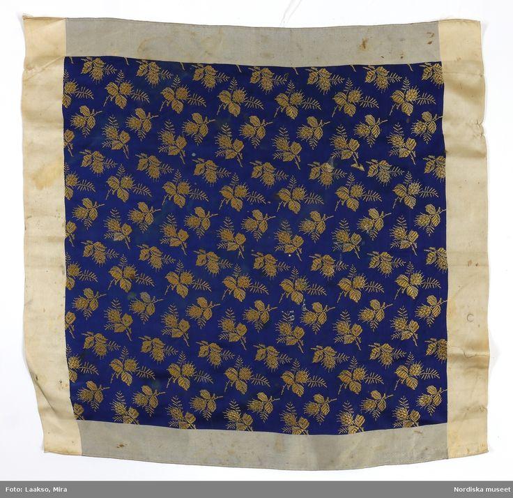 SE Östra Göinge. Halskläde av mörkblå sidenatlas med invävt mönster.