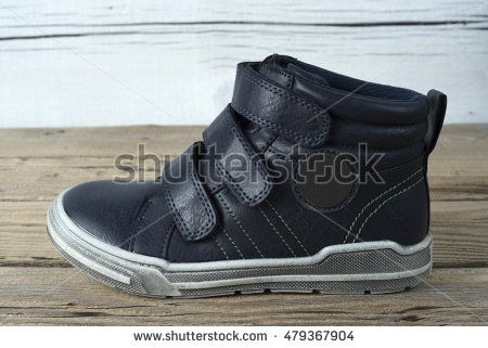 Child's shoe on old wooden table