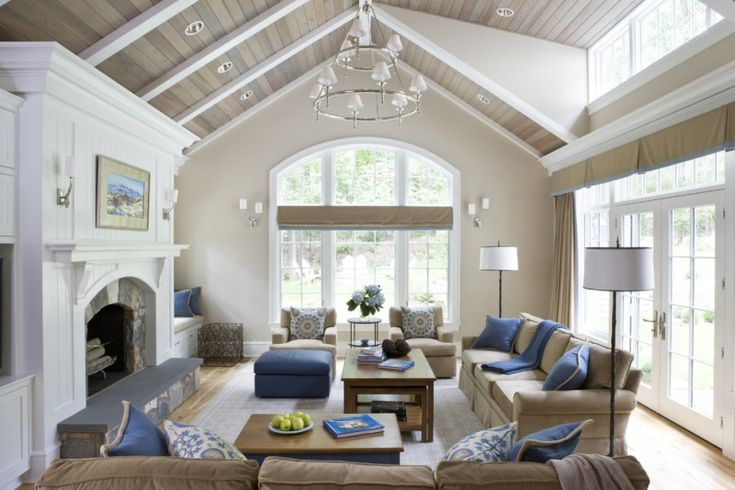 vaulted living room in white wall and ceiling, beige sofa, blue pillow, blue ottoman, white floor lamp, white chandelier  of Beautiful Ideas on Airier and Brighter Vaulted Ceiling Living Room