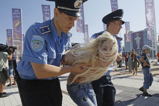 Activists of Ukrainian women's movement FEMEN protest in front of the stadium in Kiev against the visit of Belarus President Alexander Lukashenko who is attending Euro final (615×409)
