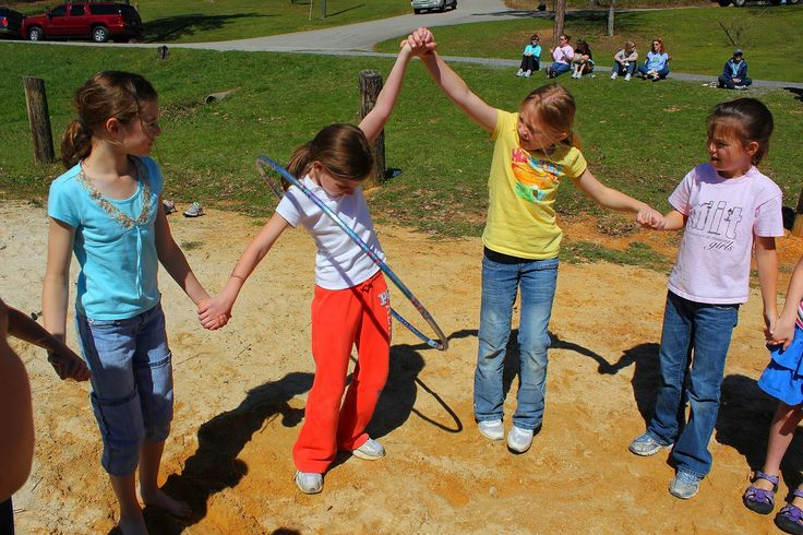 Kids pass the hoola hoop all the way around the circle without letting go of each other's hands - teamwork