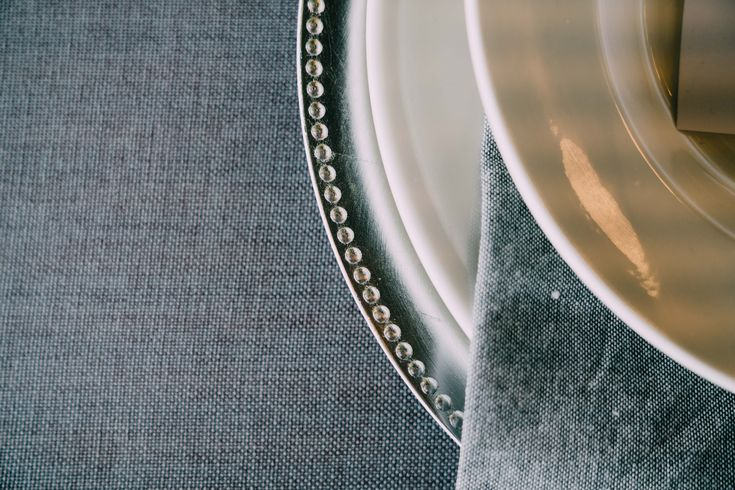 Silver charger plates, grey napkins and white plates.  Adorn Event Styling @Tailrace Centre
