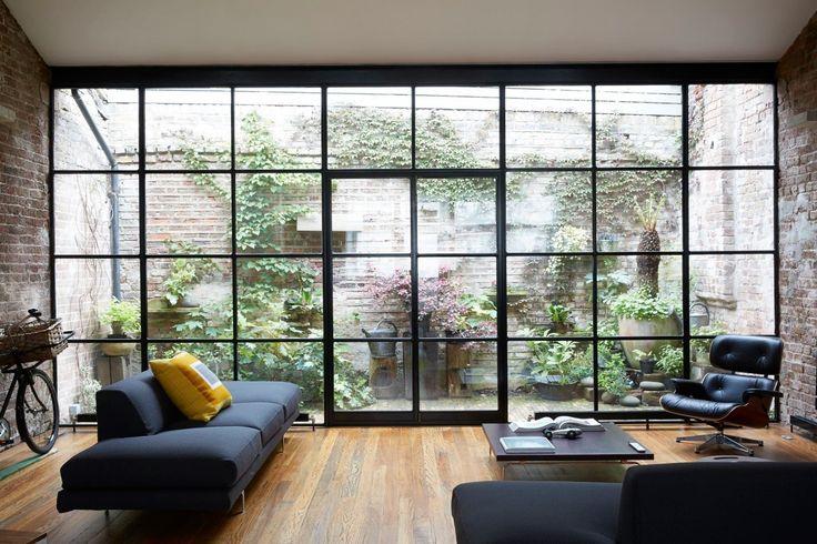 """TRANSPARENS - Wow! Stora glaspartier behöver inte vara hela, dyra glas, men det är viktigt att """"spröjsen"""" är så nätta som möjligt! Här också ett fint exempel på hur väggarna i rummet fortsätter ut på gården och får det att kännas som att de hänger ihop."""
