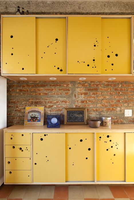 Perforated yellow cupboards and drawersresemble slices of Swiss cheese…