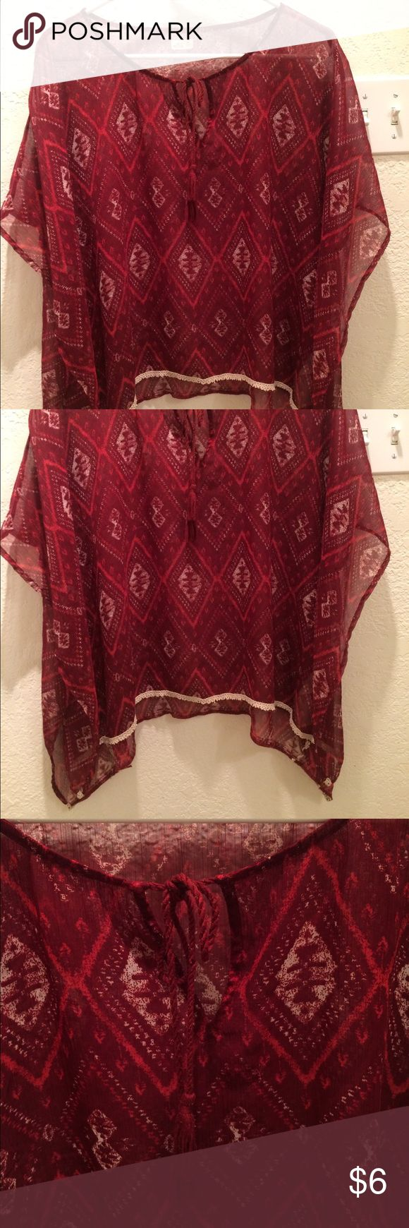 Sheer batwing style top from Hollister Sheer top  with tie detail in the front and beige lace type detail at the bottom. In good condition no holes or stains. The sleeves are a batwing style. 1OO% polyester. Size Small. Burgundy in color with red and beige details and a tribal style print Hollister Tops Blouses