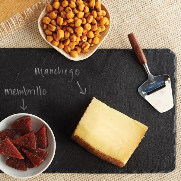 """Spanish Cheese Plate - Gifts Under $50 - Gifts & Gift Baskets Enjoy traditional tastes of Spain on a classic 8"""" x 12"""" slate serving board. Includes Spanish Salted Roasted Corn Nuts, Boska Cheese Slicer, Miguel & Valentino Quince Paste and Manchego Cheese."""