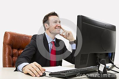 Handsome businessman smiling positively in office while using his computer.