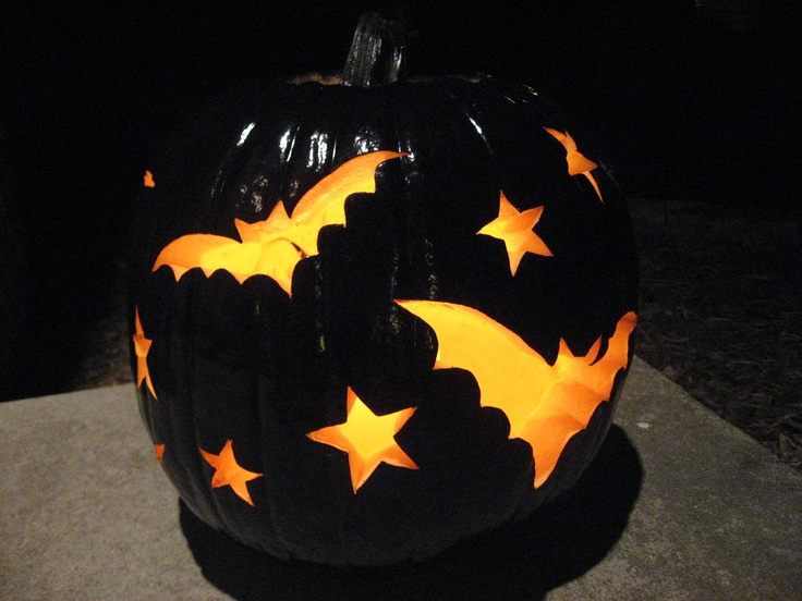 Spray paint your pumpkin black and carve it.