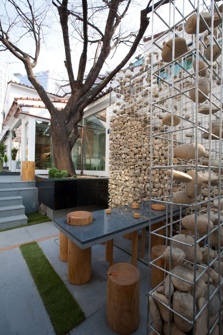 """Closeup of the gabion walls at Cafe Ato in Seoul. The """"falling"""" rocks are suspended by wires and eyebolts."""