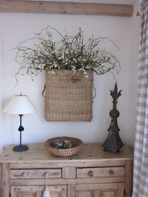flowers in a basket on the wall - these are armory baskets - used to hold shells for artillery guns