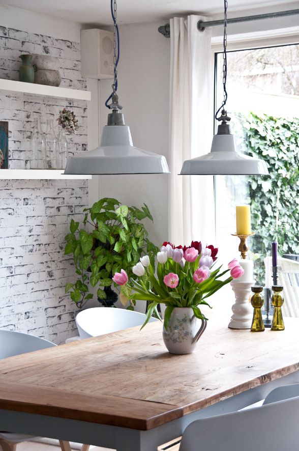 Exposed brick wall painted white aged, thick white floating shelves, fresh flowers, chunky wooden table and industrial ceiling pendants