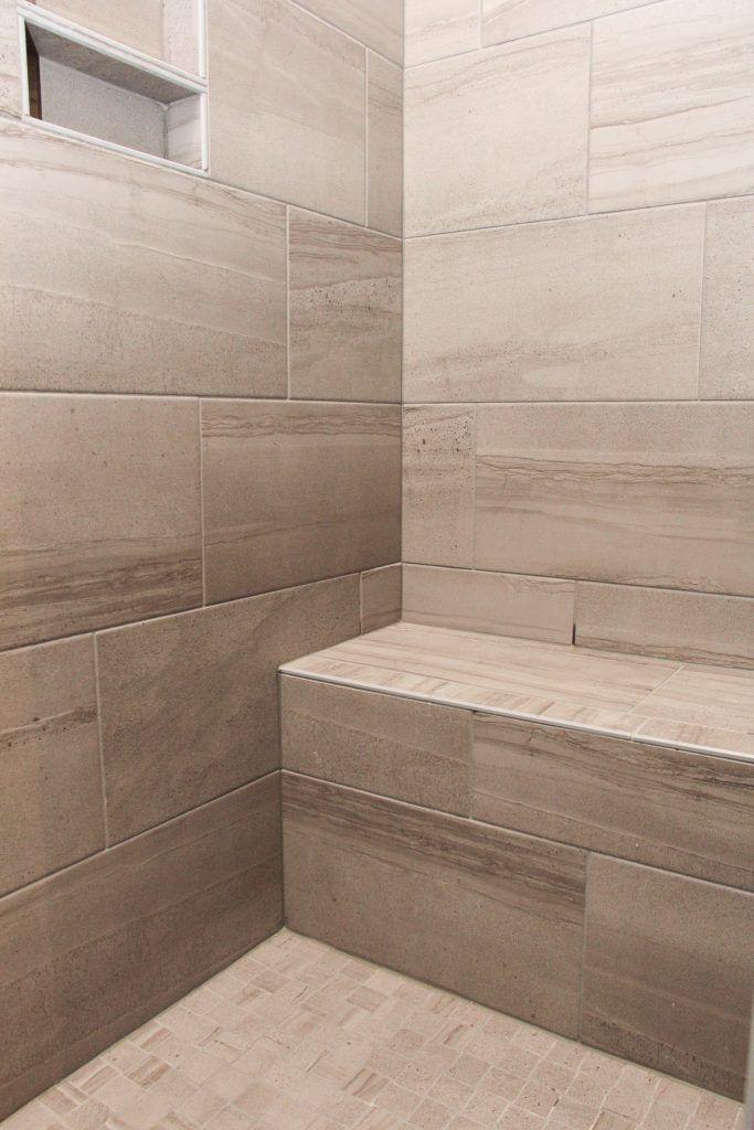 dark beige tile shower with bench