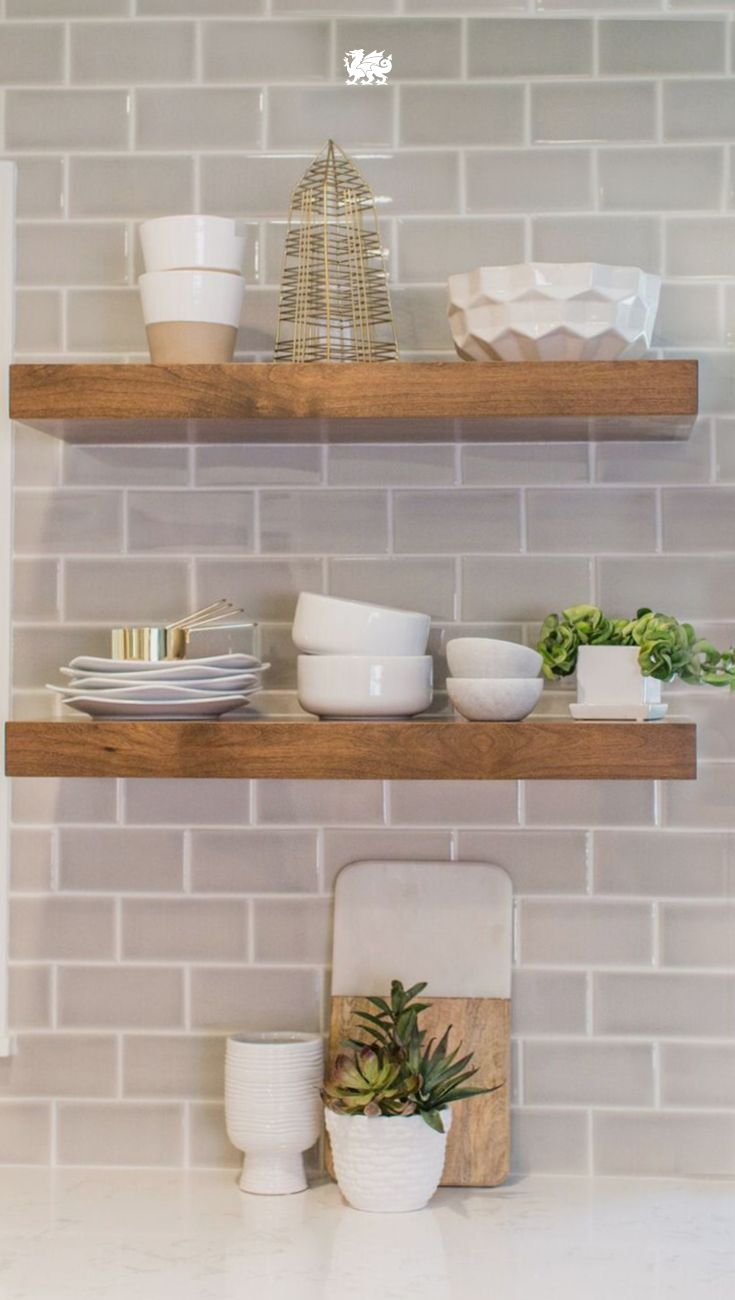Floating natural wood shelves against a subway tile backsplash makes a perfect matchup for modern farmhouse style. Open shelving above white quartz countertops is high on style and a great kitchen organization strategy. Click through to see the full renovation of this home by husband and wife design duo JKath. [Featured Design: Torquay™] CC: @jkathdesignbuil.