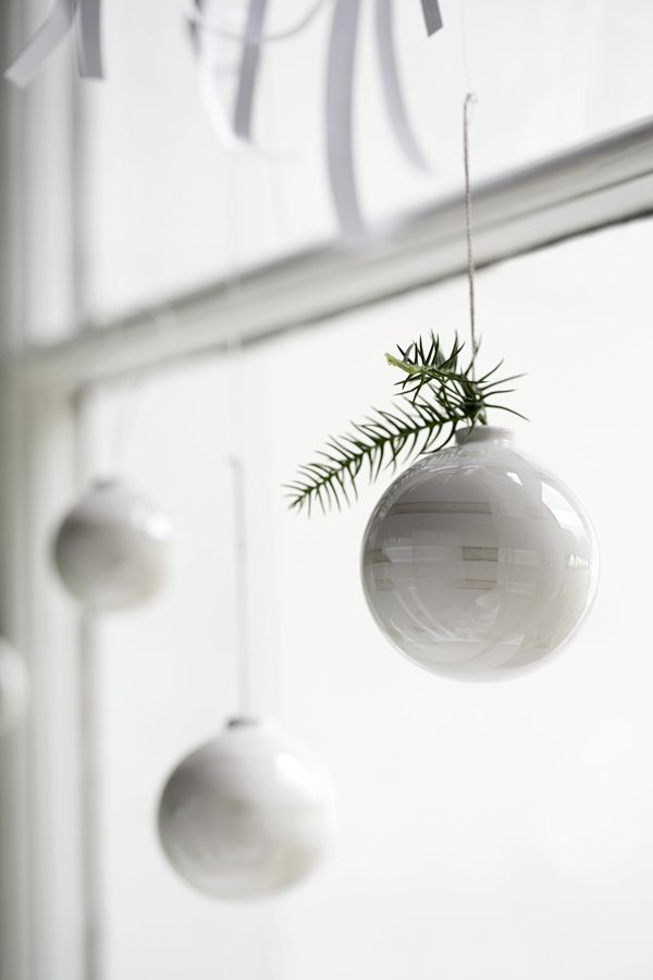 //Simple white ornaments swing in a clear, white frame.    Omaggio_christmas_baubles_closeup_High Auflösung JPG_296201