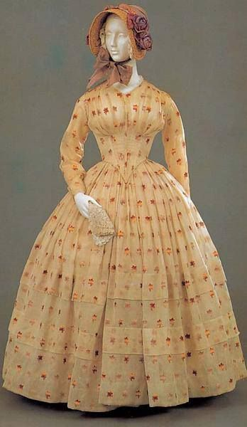 Winsome late 1840s-early 1850s dress with fitted sleeves, dropped, pointed waist, and full, tiered bell skirt.