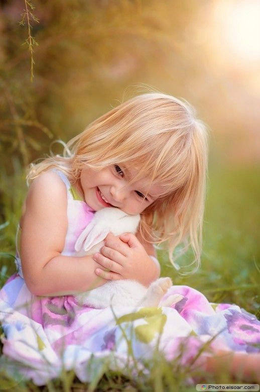 Cute Girl embraces white rabbit
