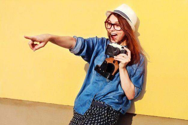 Mujer joven alegre con cámara mostrando algo con su dedo Foto Gratis