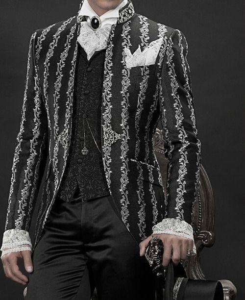 """Men Gothic Suit  -Korean frock coat in silver and black brocade woven fabric, collar with rhinestones, combined with black satin trouser, black brocade period waistcoat  Amadeus in silver lace matching with handkerchief, black cameo brooch pin with crystal rhinestones and """"Beethoven"""" collar shirt with cuff in silver lace."""