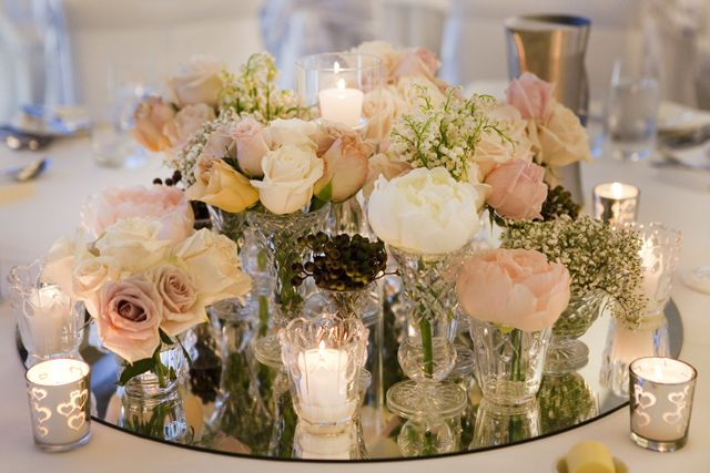 Centerpiece of Champagne & Dusty Pink flowers placed on a mirror base, surrounded with votive candles.