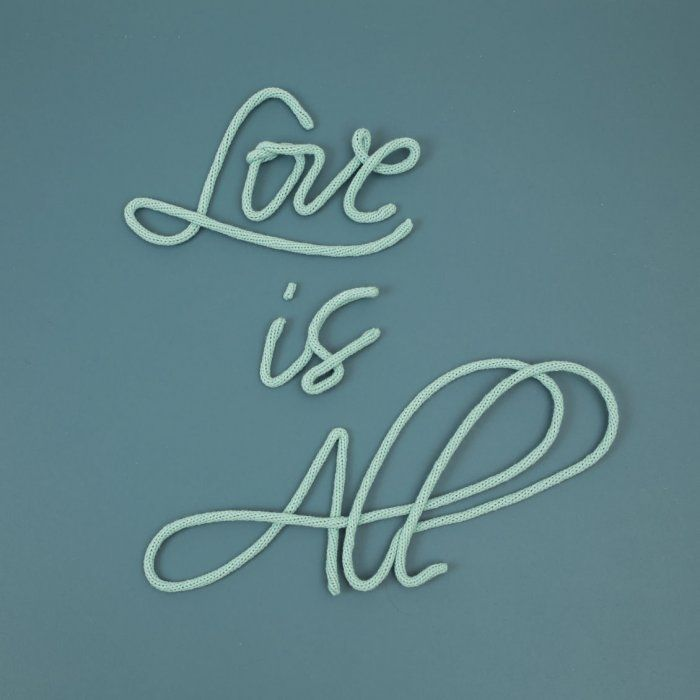"Phrase ""Love is All"" en laine"