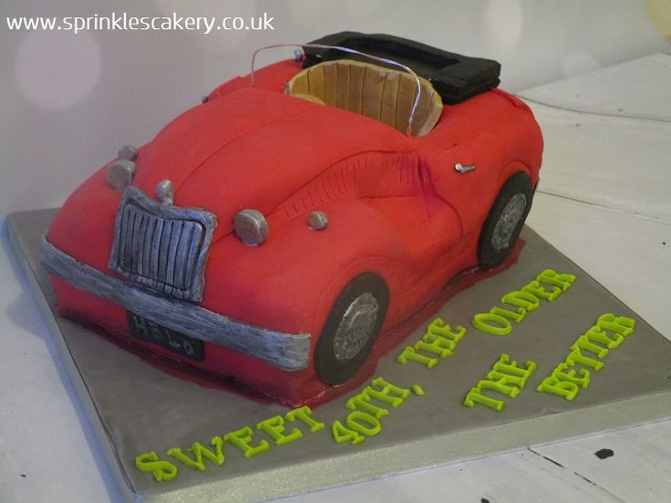"This was the first carved cake I did as the business launched... A vintage sports car... Only the windscreen was non-edible (made from flower wire). I look forward to seeing improvements if I get to make another carved car cake. This was carved from a 12"" x 8"" tin."